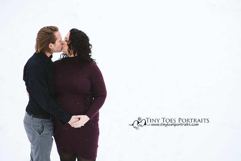 pregnant woman and husband kissing in the snow
