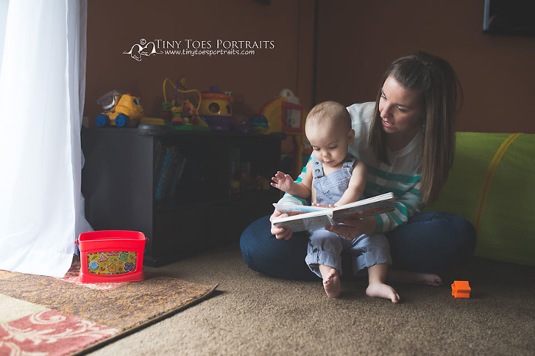 baby boy reading a book with his mom