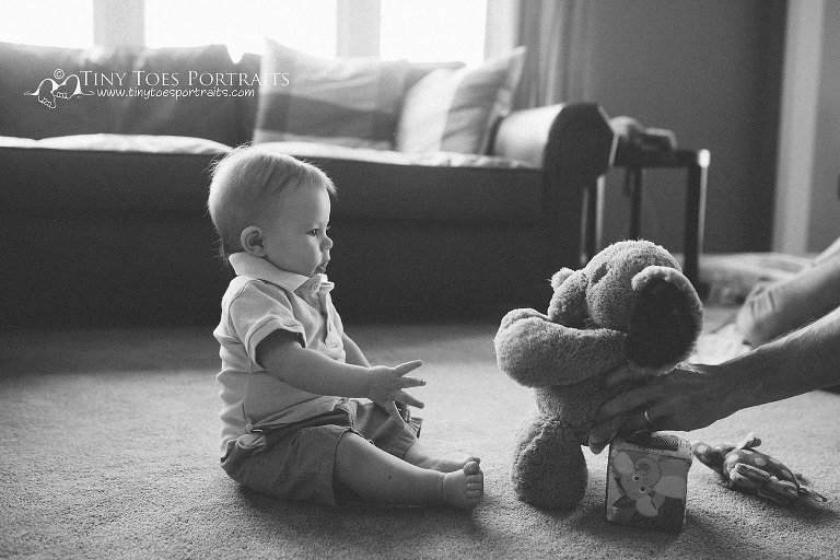 baby boy looking at his stuffed elephant