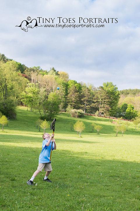 boy playing lacrosse in a field