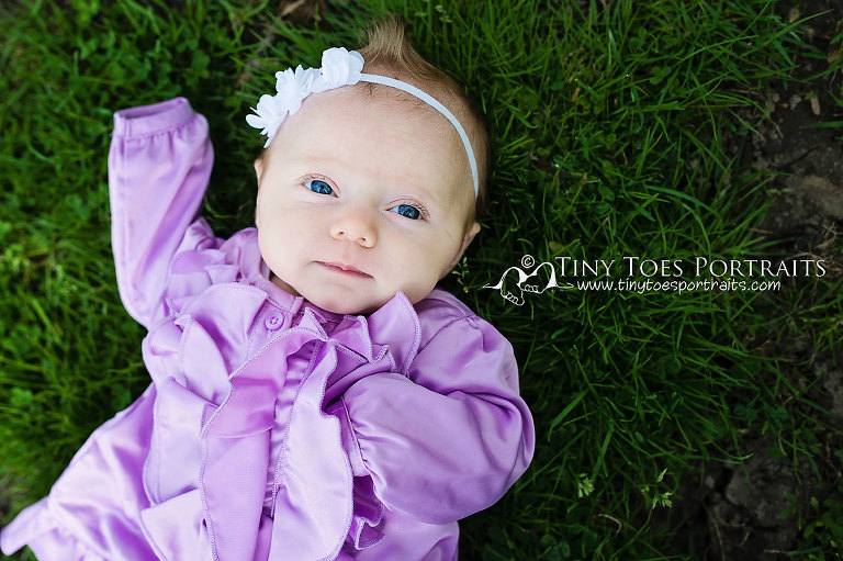 baby girl in purple lying in the grass