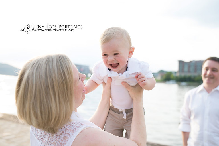 mom holding baby boy up in the air