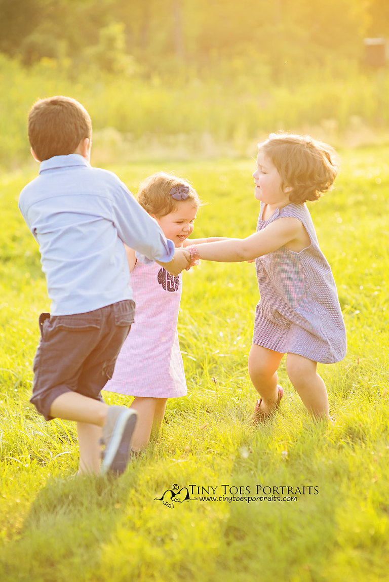 three kids playing ring around the rosie