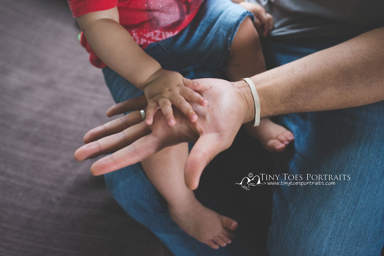 baby boys hand in his daddy's hand