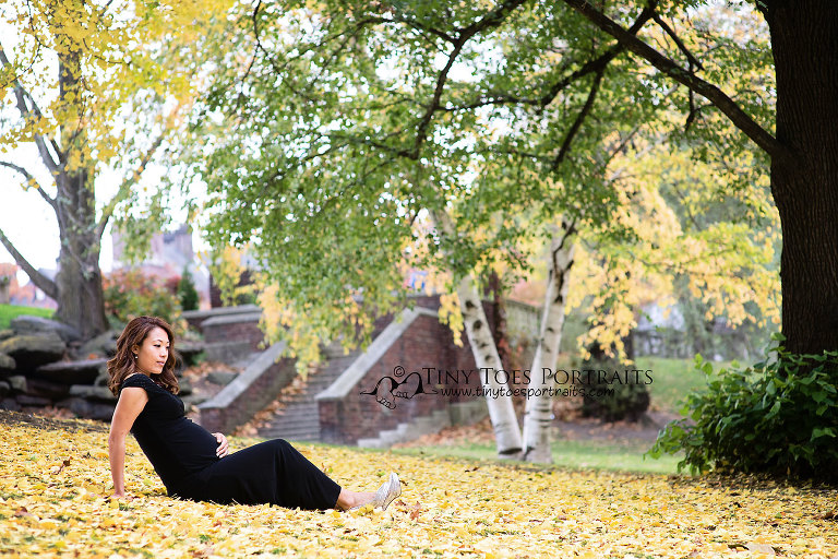 mom to be in the leaves at the park
