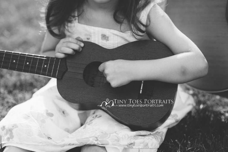 closeup of little girls hands on guitar