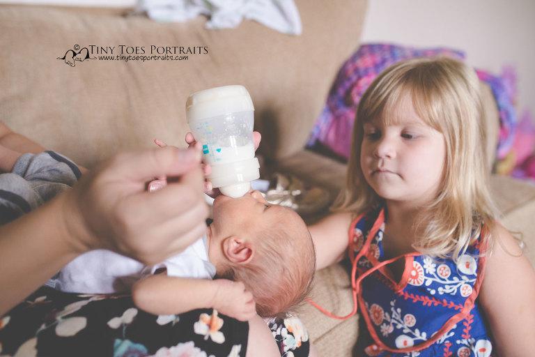 big sister feeding her newborn brother